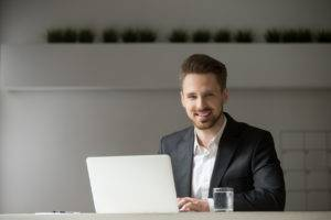Smiling young businessman in suit with laptop looking at camera